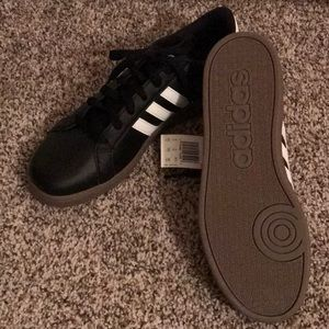 Boy's black and white adidas sneakers.